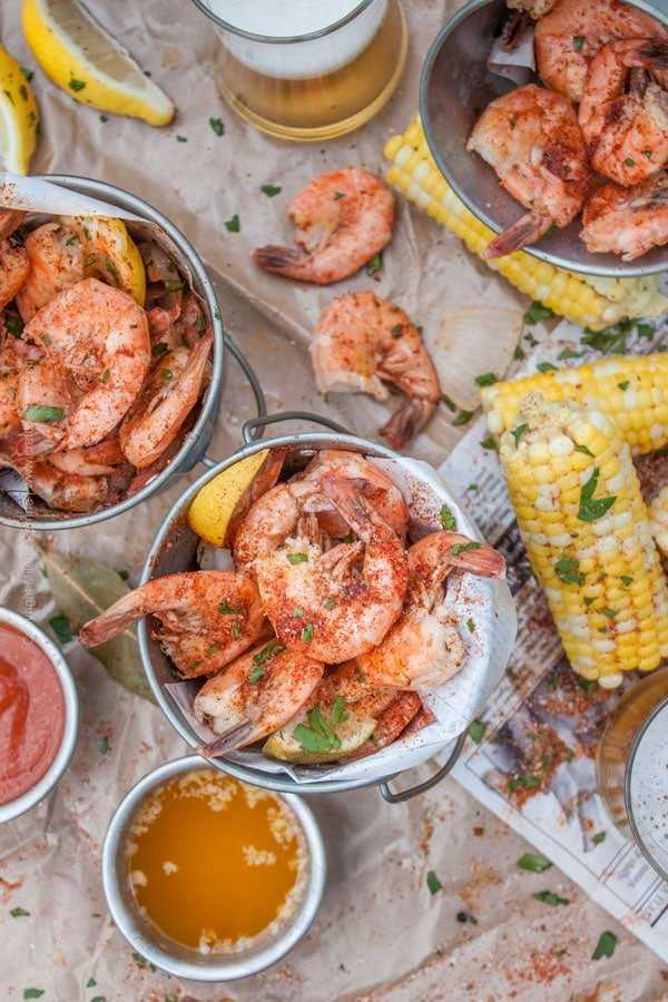Beer boiled peel and eat shrimp with parsley, drawn butter, cocktail sauce and corn.