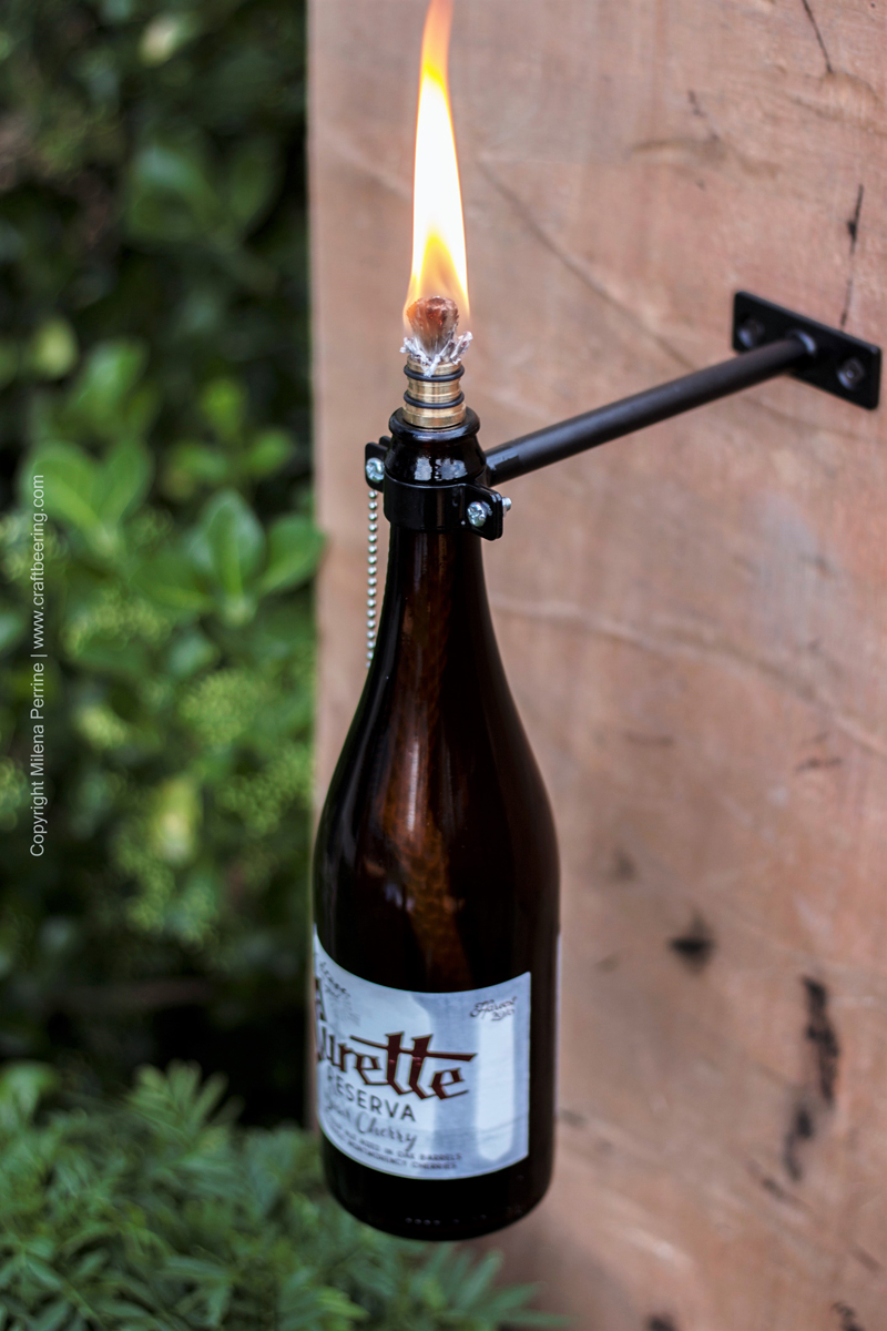 Beer bottle tiki torch mounted on wall using this kit: http://amzn.to/2uVHs8Y