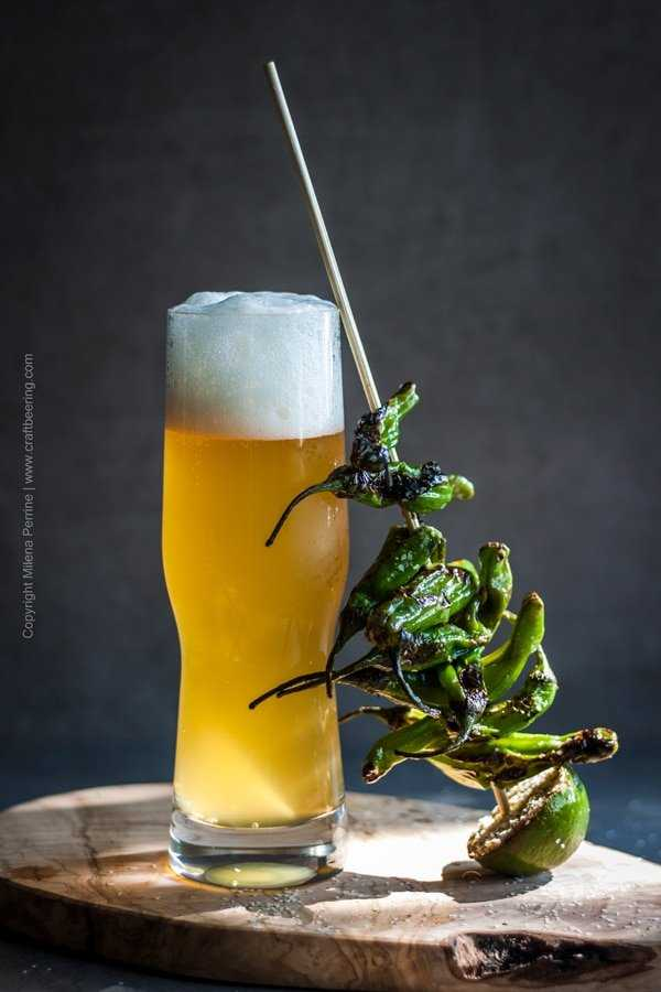 Blistered shishito peppers arranged on a skewer and leaning against an IPA filled craft beer glass.