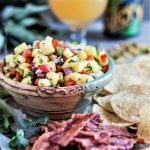 Pineapple salsa in a bowl served with bacon chips and tortilla chips