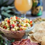 Pineapple salsa served in a bowl alongside candied bacon chips.