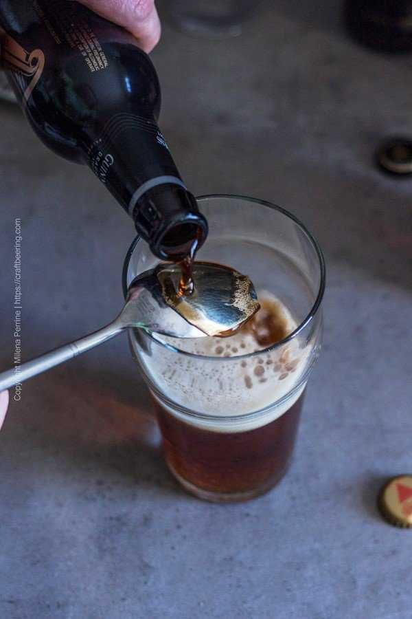 Guinness Draught stout poured over the back of a spoon to create a Black and Tan beer.