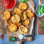 Fried mozzarella cheese appetizer served with fresh basil and Parmesan for garnish and marinara as a dip.